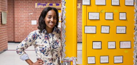 Mid shot of a young female teacher in a school hallway, smiling in front of an open yellow door full of inspirational messages about reading.