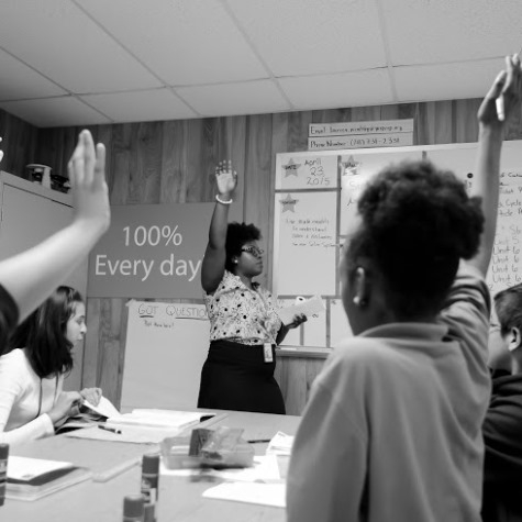 A black and white photo of students with their hands raised during a class.
