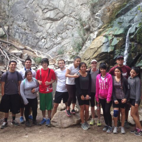 Group shot of a class of high school students posed in front of a rocky cliff wall.