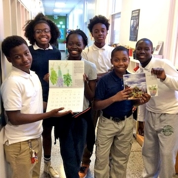 A group of middle school students in a hallway showing off pictures of plants.