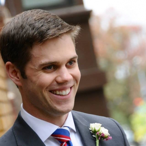 Close shot of a smiling man with short brown hair, wearing a black blazer, white shirt, red, white and blue tie, and a flower in his lapel, in an outdoor setting.