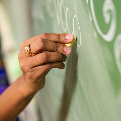 A female teacher's hand with a gold wedding right, writing on a chalkboard.