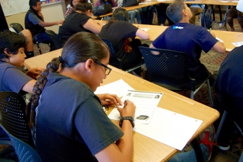 A middle school girl with long braided hair, wearing a blu tshirt and glasses, sitting at a desk, writing notes of a paper, in a classroom with her fellow students.