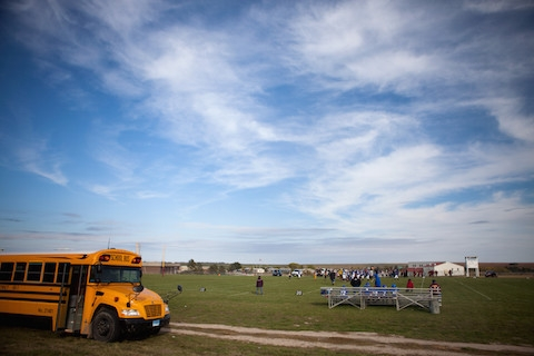A school bus parked at a football field in a rural area against a big blue sky.