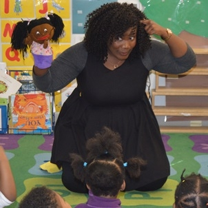 Young adult female teacher knees on a colorful rug, looking at a group of young students; she has a puppet on her right hand and points to her head with her left hand.