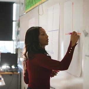 young adult female teacher stands at a white board, writing with her right hand; she wears a maroon turtleneck sweater