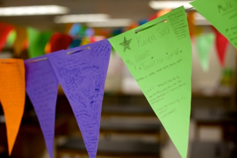 An image of brightly colored triangle-shaped flags hung in a classroom.