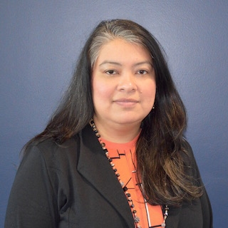 A middle-aged Latina woman with long dark hair, wearing a dark suit and coral blouse.