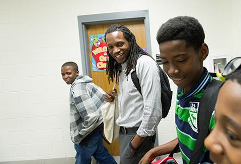 A young male teacher with dreadlocks leads a group of smiling students down a school hallway.