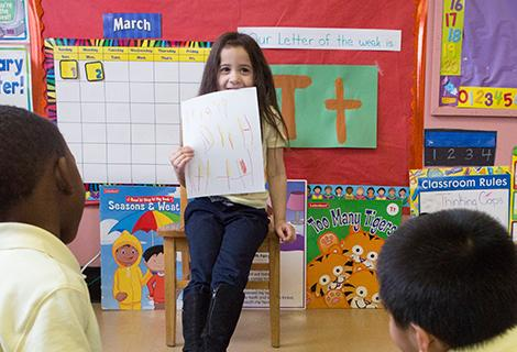 An elementary school girl with long brown hair shows off a drawing at the front of a classroom.