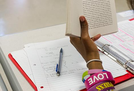 Close shot of a female student's hand holding a novel above an open note book.