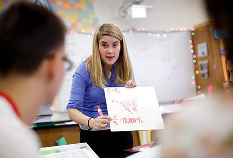 A young female teacher with long blonde hair works through a math problem on a handheld whiteboard at the front of a classroom.