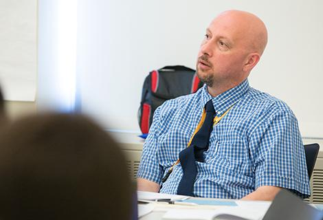 A male teacher with a shaved head in a blue shirt sits at his desk, listening to a student's question.