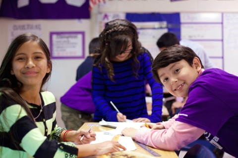 A female middle-school student with long brown hair and a male student with short brown hair and a purple shirt smile at the camera, while a female student works head down at their table.