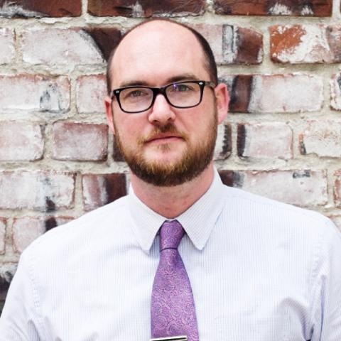 Head shot of a middle-aged man with receding hair, a brown beard, and black framed glasses standing in front of a brick wall in a white dress shirt and purple tie.