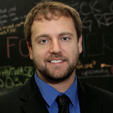A head shot of a middle-aged man with curly blond hair and a beard smiling in front of a blackboard full of colorful writing, wearing a black blazer, a blue dress shirt, and a black tie.