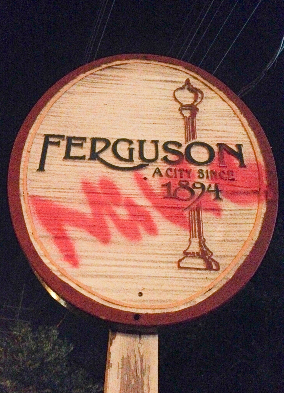 "A wooden circular Ferguson signpost with the word ""Mike"" spray painted on in red."