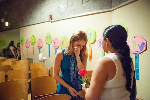 A young blonde schoolteacher crying as a student hands her a pink rose in a school auditorium.