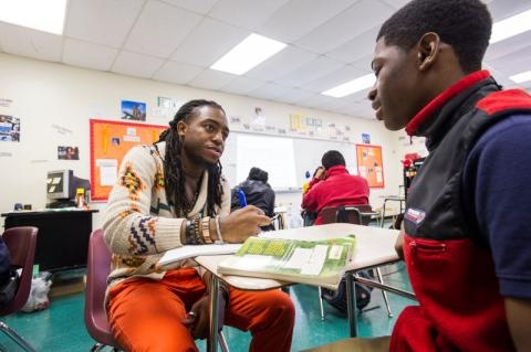 A young male teacher with long dreadlocks sits against a student's desk to help him with a problem.