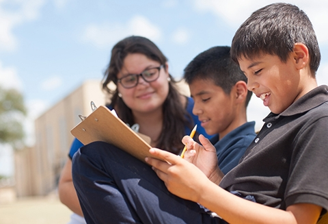 A young female teacher with wavy brown hair oversees two middle school boys working on filling out forms on a clipboard in a schoolyard.