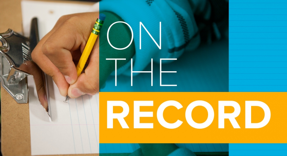 "A rectangular logo with a young child's hand writing on a piece of paper in the background, and white text reading ""on the record."""