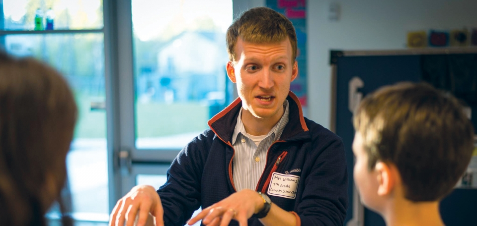A young man with short blond hair wearing a blue coat with a name tag explaining a concept to two middle-school students.