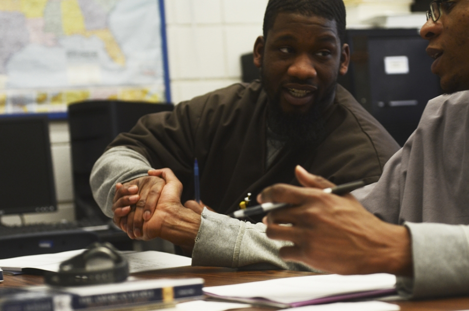 Two young adult males shake hands while sitting next to each other at a table in a classroom.