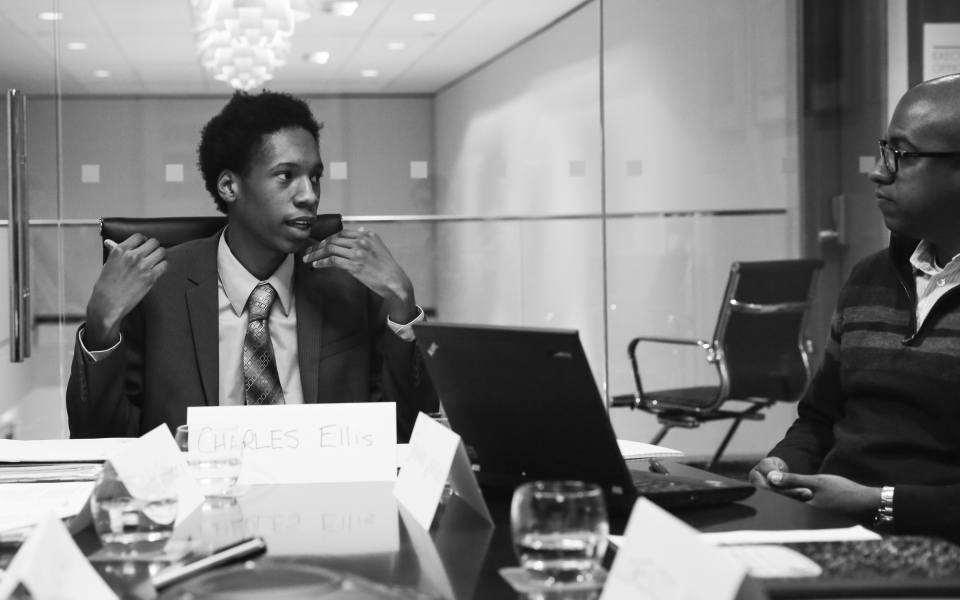 A high school student in a suit and tie sits at the end of a conference table and has a discussion with a young adult male who sits behind a laptop computer - photo shot in black and white.