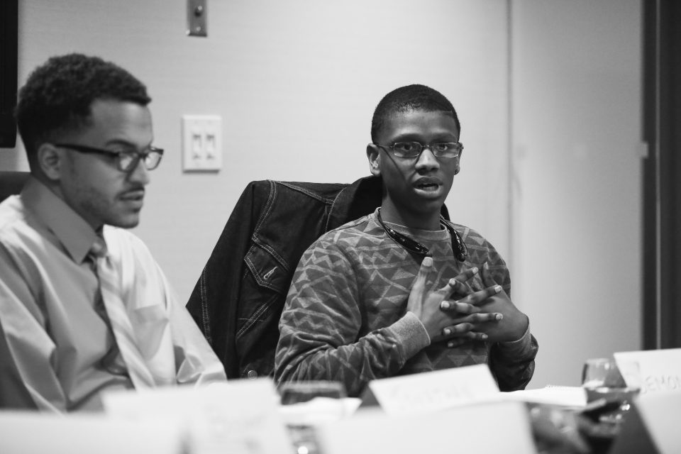 High school student sits at a conference table speaking aloud, another high school student sits next to him - photo shot in black and white.