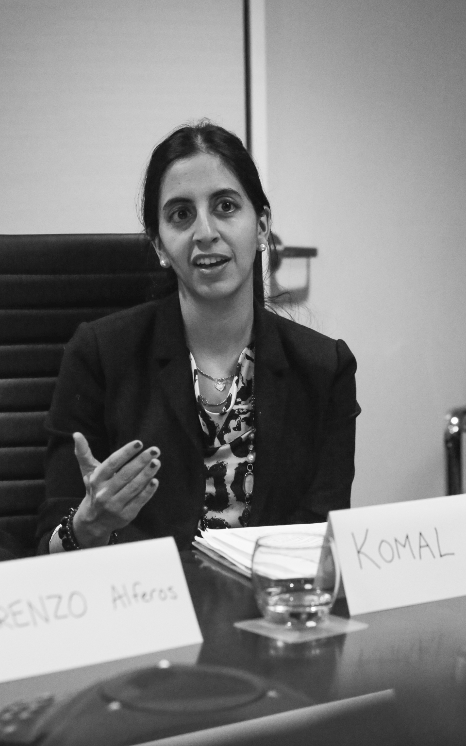 "Young adult female sits at a conference table, with a glass of water and a name tag reads ""Komal"" in front of here - photo shot in black and white."