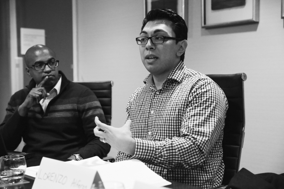 A young adult male in glasses and a button-down shirt sits at a conference table next to another young adult male speaks his thoughts - photo shot in black and white.