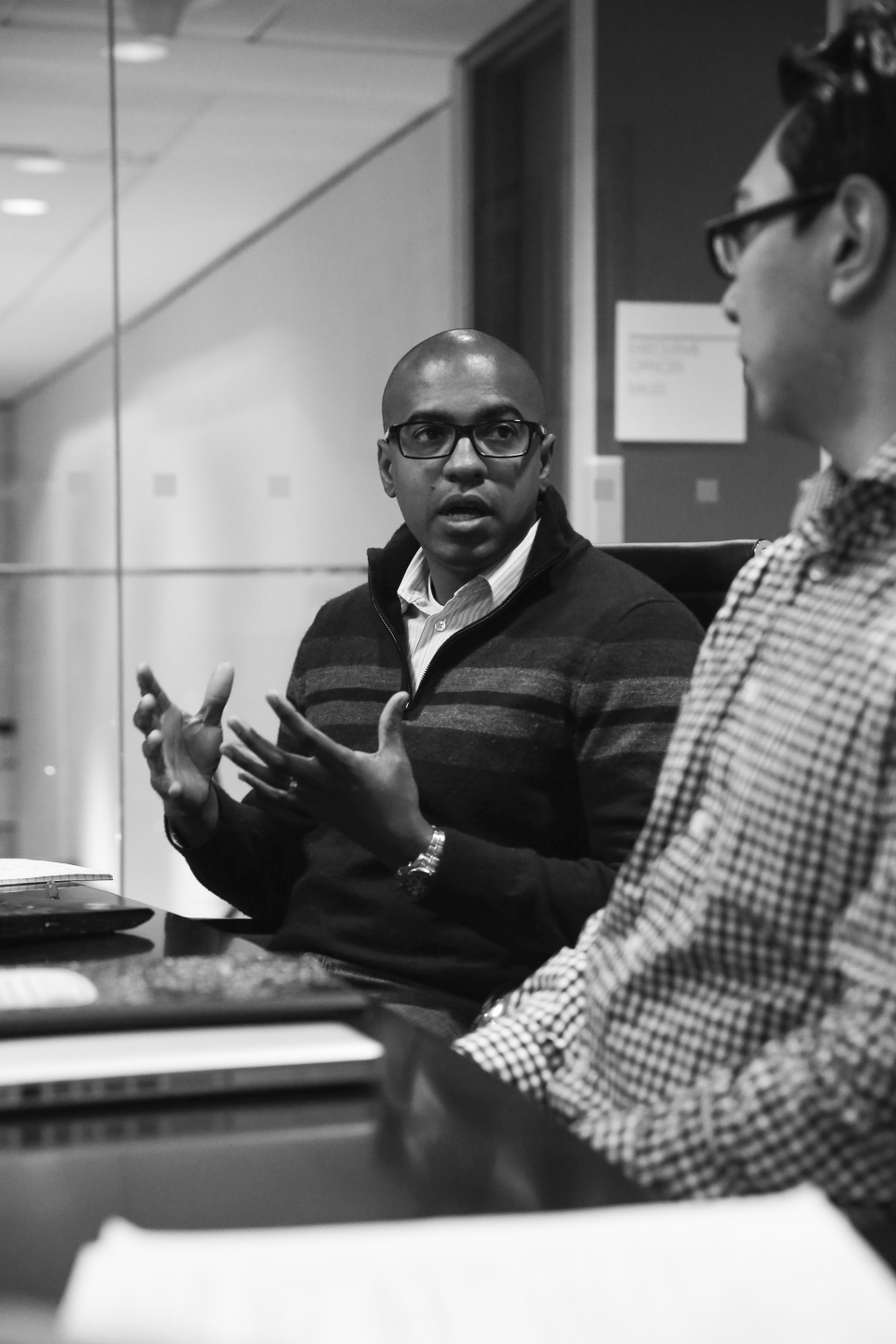 A young adult male in a sweater and glasses seated at a conference table talks to another male - photo shot in black and white.
