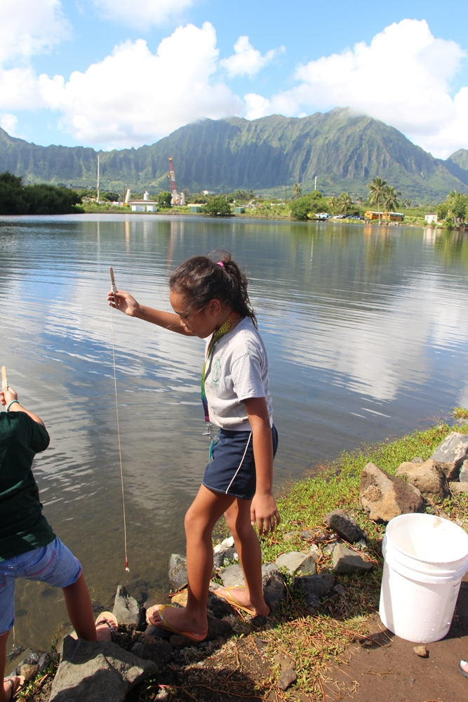 A young girl in shorts and a t-shirt and a second indistinguishable kid stand on a side of a large lake with mountains in the background; the girl holds a homemade fishing rod in her hand.