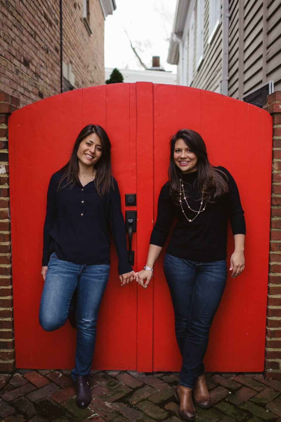 Two smiling young adult females in black sweaters and jeans stand against a bright red gate, with their pinky fingers interlocking.