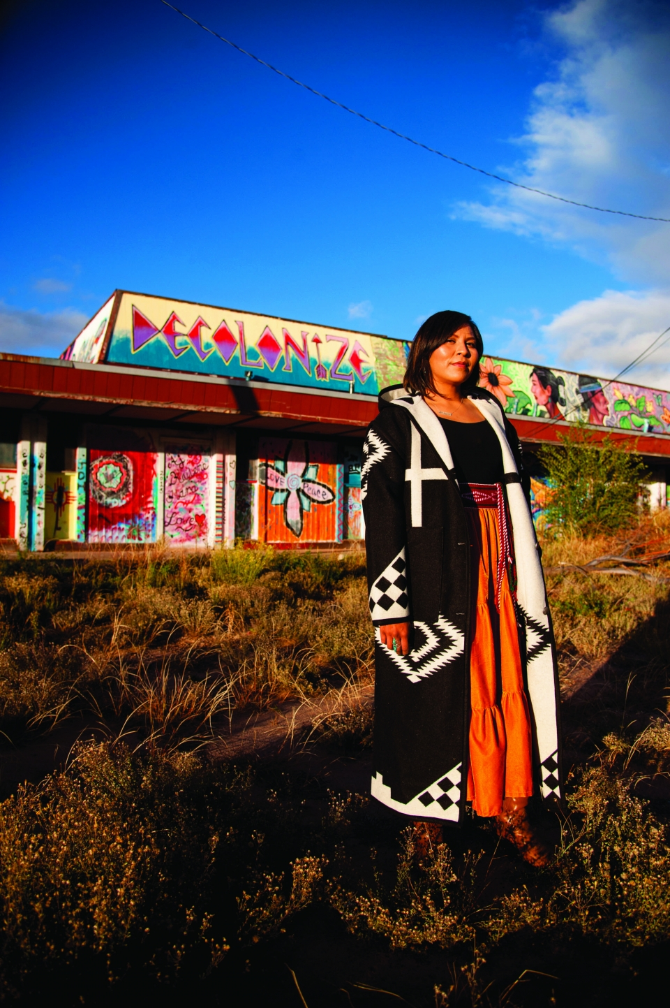 """A young adult female wearing a long traditional Navajo dress stands in a field; a bright, colorful mural painted on the side of a building is behind her, with the word """"Decolonize"""" painted at the top."""