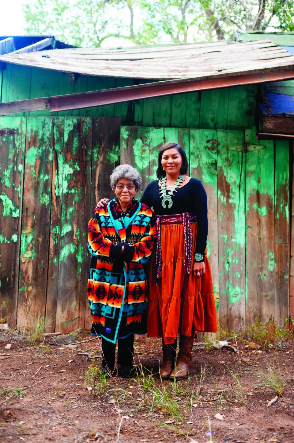 A young adult female and an older, short lady stand together, both wear bright Navajo dress; a wooden shack, partially painted green, is behind them.