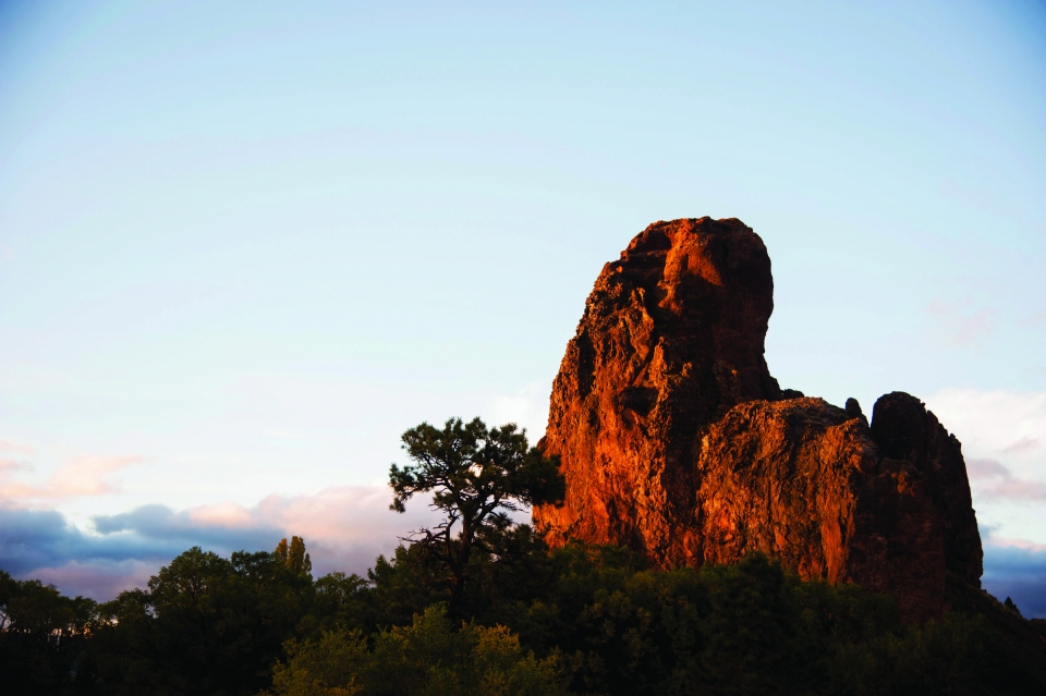 A large red rock formation and tree, with the sun setting in the background.