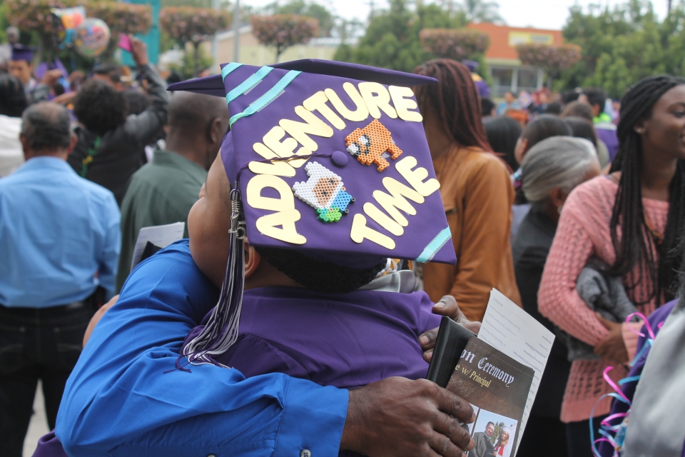 """A middle-school aged graduate in a purple gown being hugged, wearing a purple mortarboard with bead art and the words """"Adventure Time"""" on it."""