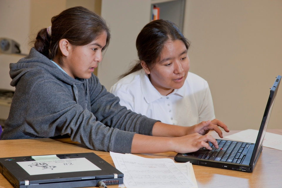 A middle-aged female teacher with long straight black hair tied back watches as a middle-school aged girl with long straight black hair works on a black laptop at a school table.