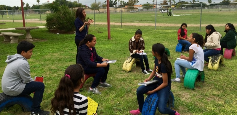 A teacher in a blue shirt speaking to her class while they are sitting outside, in a park, on seats made of painted tires.