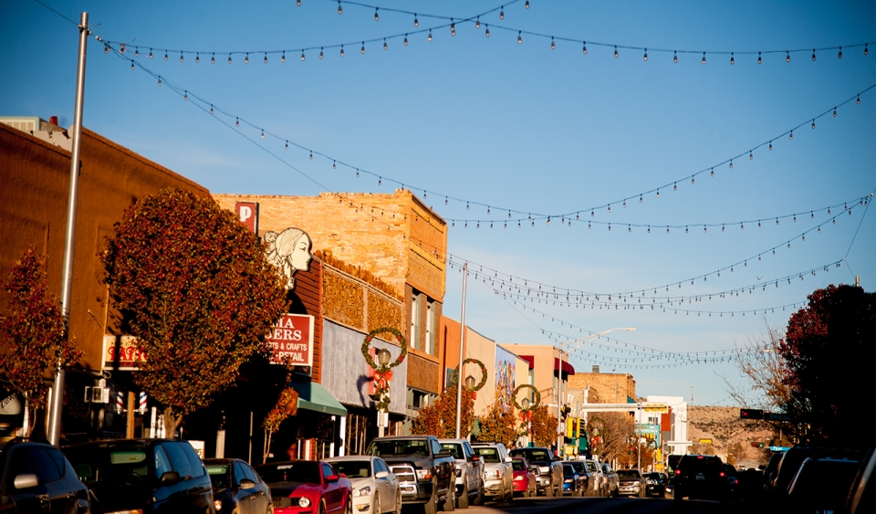 A street in on a main road in a small town, with brick buildings lining the sides of the street, cars parked, and several strands of Christmas lights connected by tall poles are strung across the street; Christmas wreaths are tied to the tops of the pole.