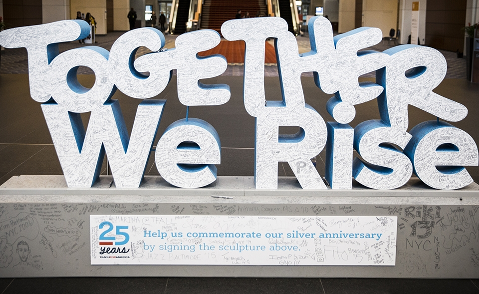 "A stone sculpture of the words ""Together We Rise"" on a cement base with a white sight with blue print and a bunch of signatures and cartoons all over it, in the center of a large entryway."