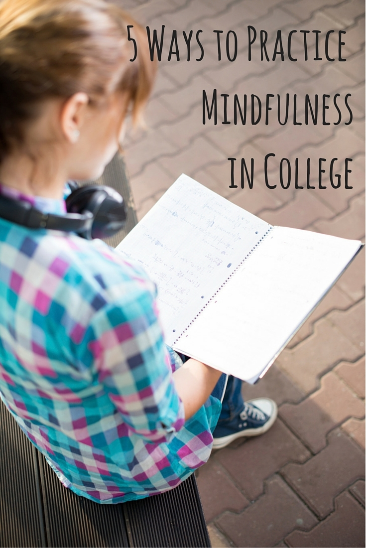 "Soft shot from behind of a woman in a blue and pink checked shirt sitting on a bench and holding a notebook in front of her with both hands and a script in the upper right corner saying ""5 ways to practice mindfulness in college."""