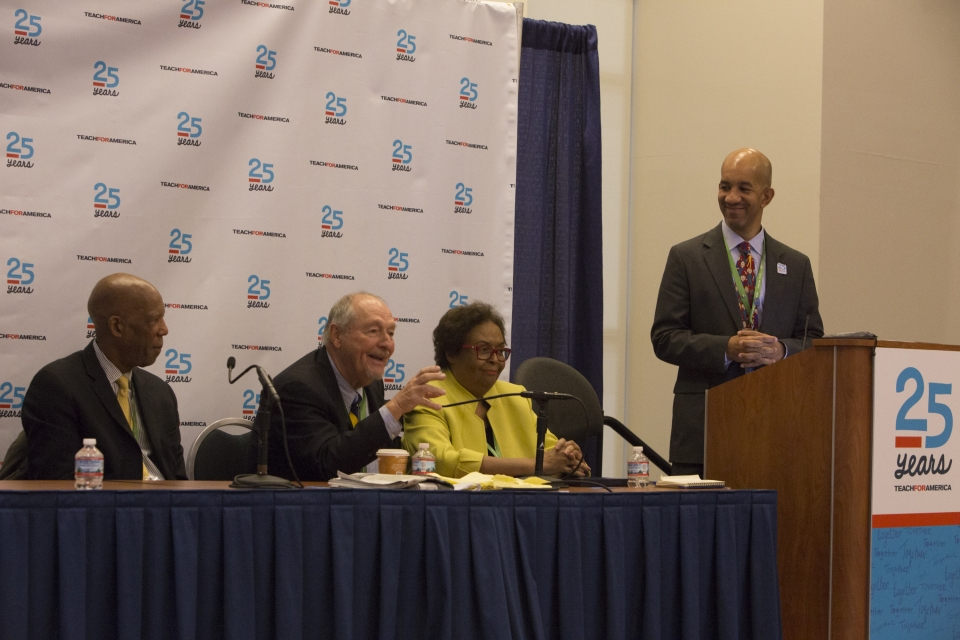 A screenshot from a video showing a man with shaved head wearing a gray suit behind a podium next to a panel of an older woman and two older men.