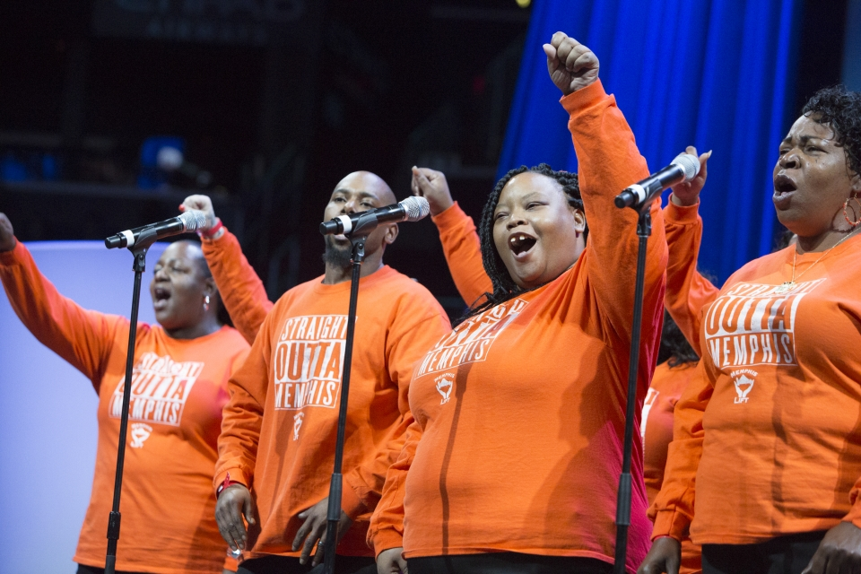 "Three woman and a man wearing orange sweatshirts saying ""Straight Outta Memphis"" stand singing into microphones with their fists in the air with a blue curtain in the background."