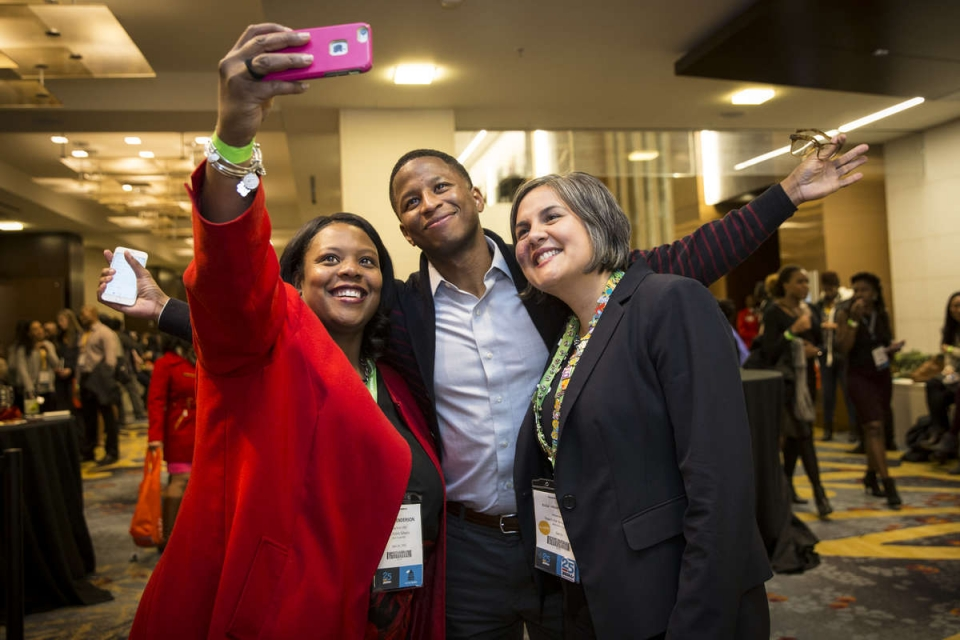 Two young teachers taking a selfie with a middle-aged woman with gray hair in a blue blazer.