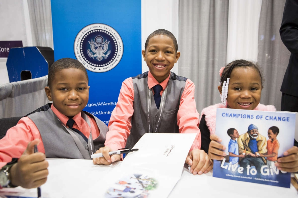 Three young children in dress clothes show off a children's book at an exhibition booth.