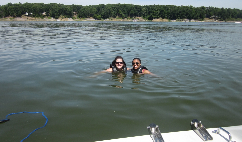 Two smiling young adult females in sun glasses and life jackets wade in a large lake.