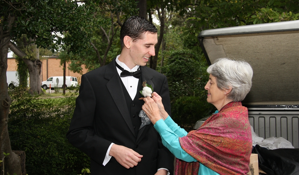 An older female with white hair pins a corsage to a young adult male in a tuxedo; both stand outside with trees in the background.