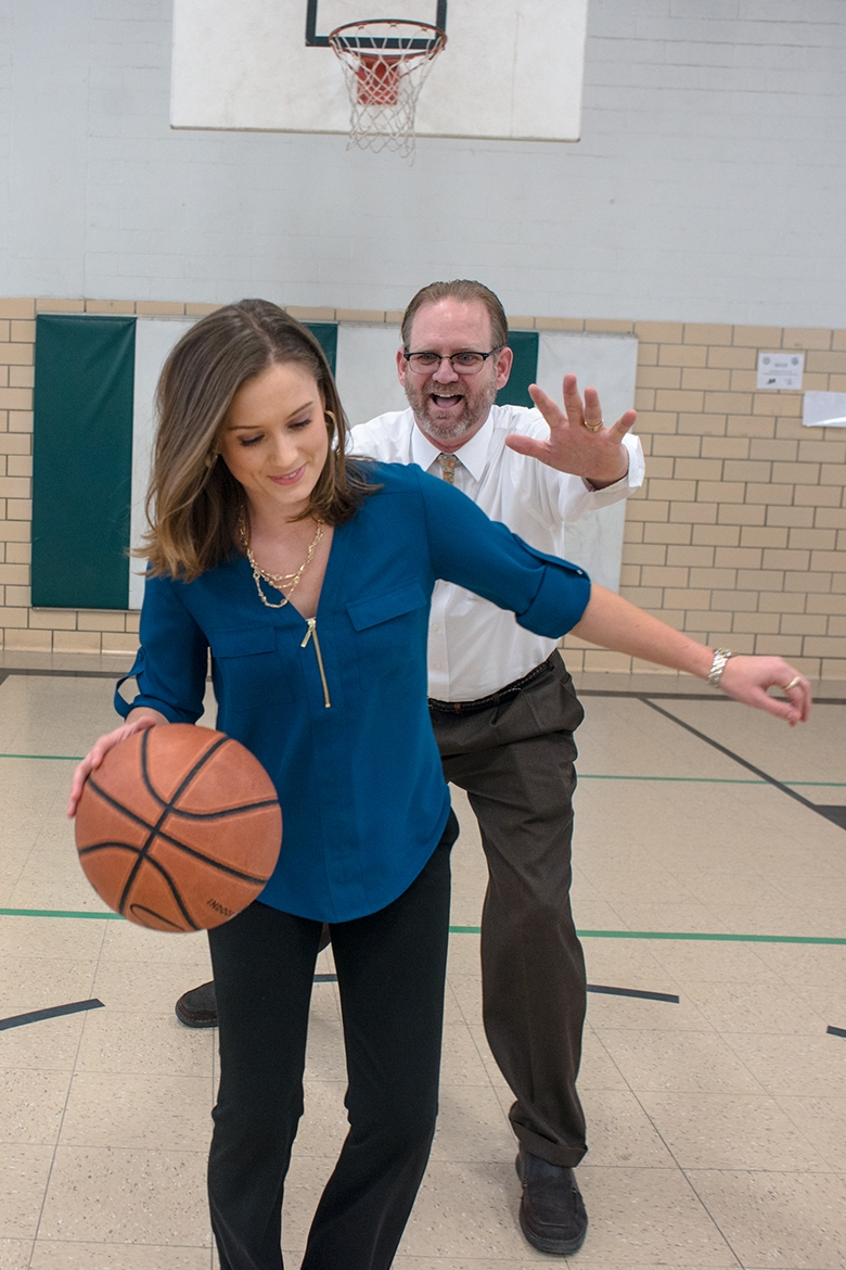 A young adult female in business casual clothing bounces a basketball, an older male stands behind her blocking her shot, both stand in a gymnasium by a basketball hoop.